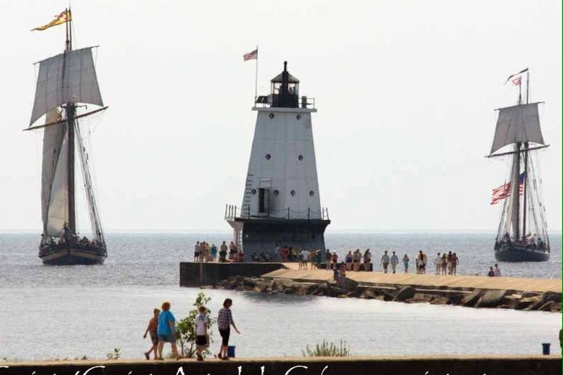 Ludington Lighthouse with tall sailing ships.